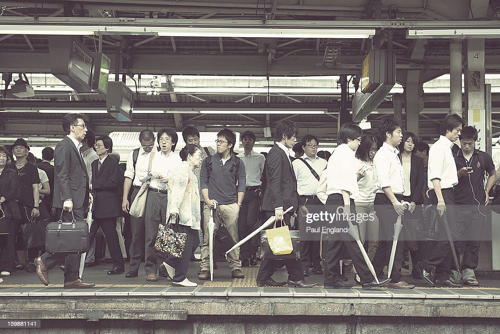 CONTENT] Morning commuters wait on a train on a crowded platform at Shinjuku Station