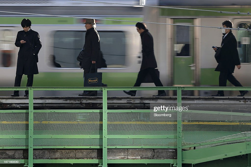 Morning commuters walk along a platform at a train station in Tokyo, Japan, on Thursday, Nov. 29, 2012. Japan's cabinet approved a second round of fiscal stimulus worth 880 billion yen ($10.7 billion) using budget reserves as Prime Minister Yoshihiko Noda attempts to boost the economy before elections on Dec. 16. Photographer: Kiyoshi Ota/Bloomberg via Getty Images