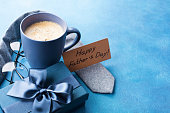 Morning cup of coffee, gift box, necktie and eyeglasses on blue table for greeting on Happy Fathers Day.