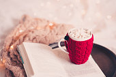 Knitted cup of coffee on open book with knitted scarf in bed over Christmas lights closeup. Good morning.