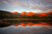 Beautiful alpine glow on Hallet Peak and the Continental Divide. The mountains reflect in Sprague Lake. This beautiful lake is located in Rocky Mountain National Park outside of Estes park Colorado