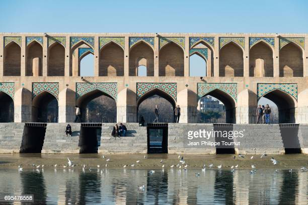 A morning in Isfahan, Iranian people relaxing on Khaju Bridge on the Zayandeh River (Isfahan, Iran)