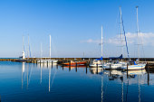 Skanor, Sweden - Windless and tranquil morning in the marina with sailboats and motionless sea. Logos and id removed.
