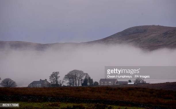 Morning mist hangs behind cottages in Borrow Beck in Cumbria