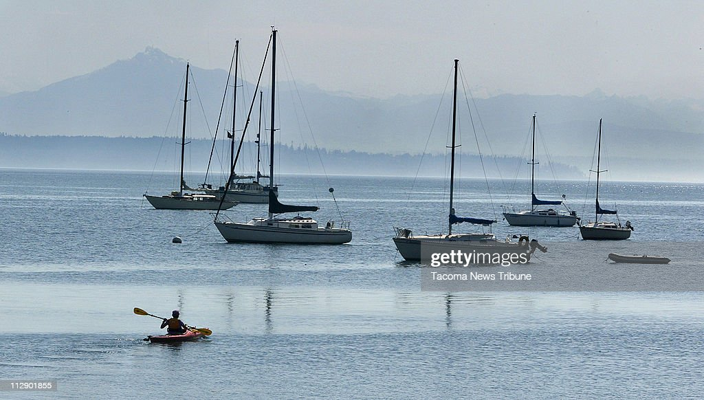 Morning mist obscures the North Cascades as Joan Manchester of Colorado sets out from the Langley Marina in a kayak rented from the Whidbey Island Kayaking Company, Tuesday, June 2, 2009.