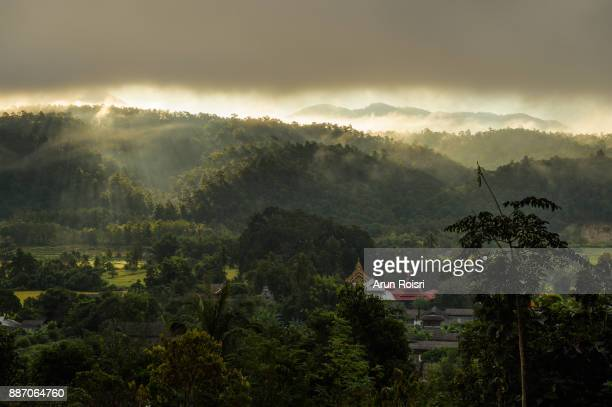 Morning mountain landscape with waves of fog at Muang Pon, Mae Hong Son province, Northern Thailand. Waves of clouds in the background peaks covered with coniferous deciduous forests