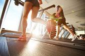 Female athlete in mini shorts warming up on treadmill on beautiful sunny morning