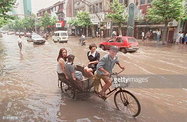 A morning rainstorm flooded Shanghai as this owner of a tricycle makes some extra money paddling three people through Huaihai Road 25 June To keep...