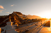 Morning rays in Lhasa valley with traffic passing in front of Potala palace.
