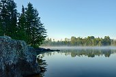 Morning Reflections of a Forest on a Foggy Wilderness Lake