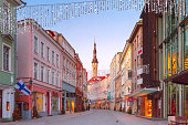 Beautiful illuminated street of Medieval Old Town and Town Hall in the morning blue hour, Tallinn, Estonia