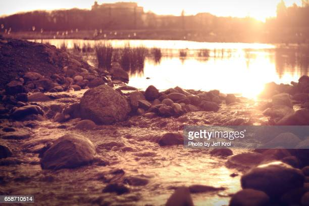 Morning sunset over stream, flowing water with rocks, nature and sun glowing at down, lake in the background