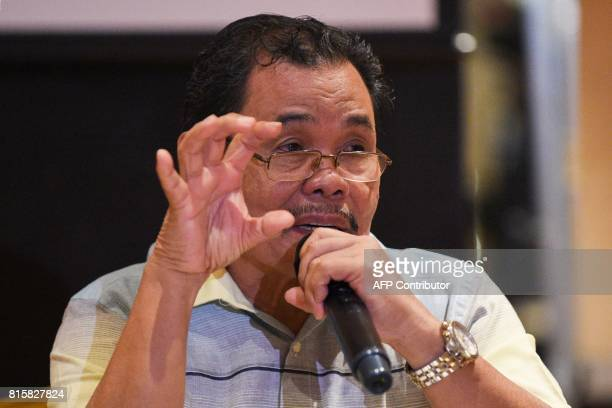 Moro Islamic Liberation Front peace panel chairman Mohagher Iqbal gestures as he answers questions from mebers of the media after the signing...