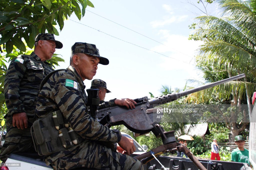 Moro Islamic Liberation Front (MILF) rebels man a machine gun near the venue where Philippine President Benigno Aquino will be attending a ceremony as part of his visit to the rebels stronghold in Sultan Kudarat, on the southern island of Mindanao on February 11, 2013. Philippine President Benigno Aquino paid a historic visit February 11, to the stronghold of Muslim rebels and said peace talks with them must be speeded up. AFP PHOTO/Richele Umel