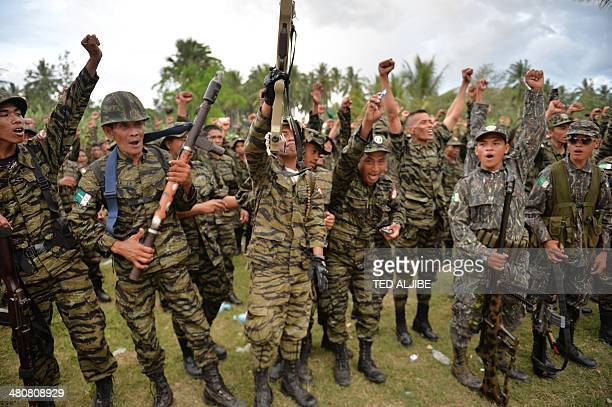 Moro Islamic Liberation Front rebels shout 'Allah akbar' as they celebrate the signing of a peace agreement during a rally at Camp Darapanan in the...