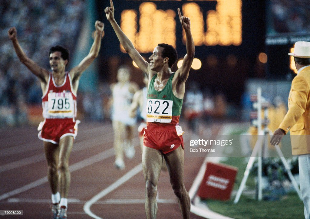 Moroccan athlete Said Aouita celebrates as he crosses the finish line in first place to win the gold medal in the Men's 5000 metres event at the 1984...