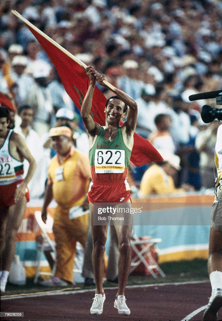 Moroccan athlete Said Aouita celebrates with the national flag after crossing the finish line in first place to win the gold medal in the Men's 5000...