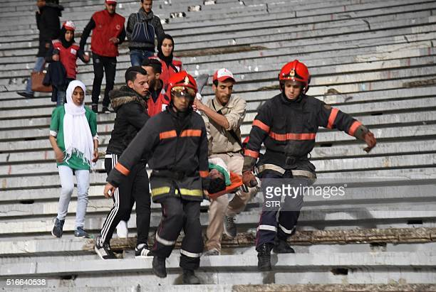 Moroccan emergency personnel carry an injured supporter following clashes between rival fans of Raja de Casablanca football club at the end of their...
