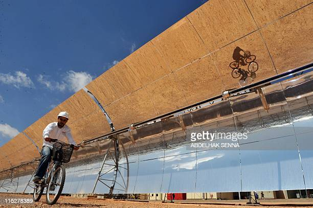 A Moroccan engineer cycles past the solar panels of the solar power station of Ain Beni Mathar near Oujda on May 31 2011 201 The station provides 13%...