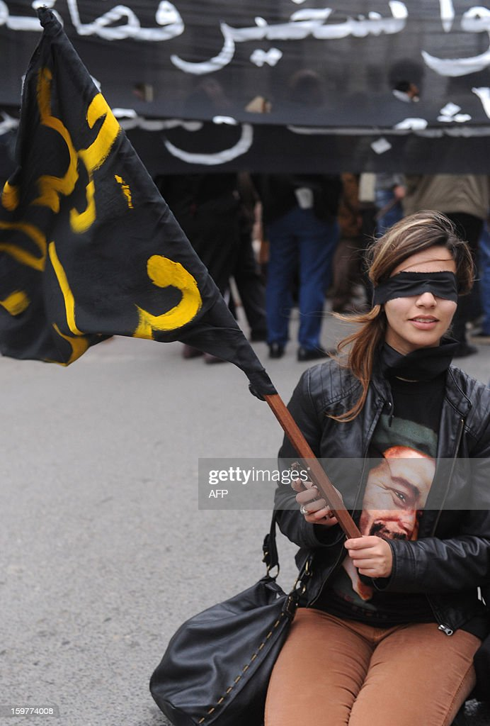 A Moroccan 'February 20' movement activist covers her eyes and holds a banner as she takes part in a demonstration to demand the release of political prisoners, in Rabat, on January 20, 2012. Over 100 protesters shouted slogans, demanding 'freedom and dignity,' and waved banners during the protest, in a suburb of the capital, as a large deployment of riot police stood guard nearby. AFP PHOTO/FADEL SENNA
