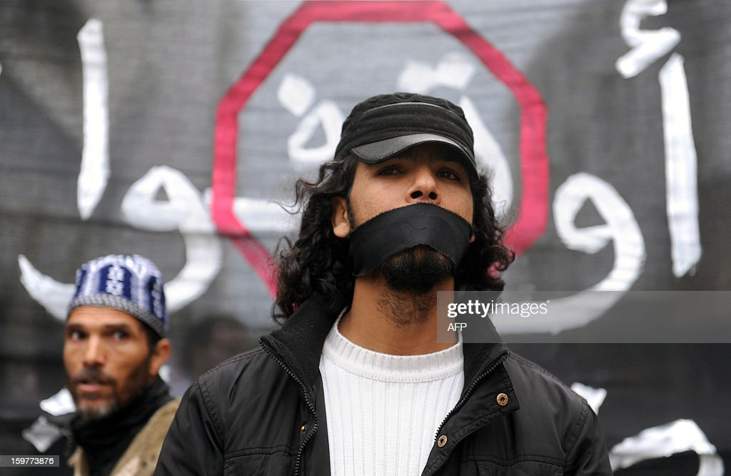 A Moroccan 'February 20' movement activist covers his eyes as he takes part in a demonstration to demand the release of political prisoners, in Rabat, on January 20, 2012. Over 100 protesters shouted slogans, demanding 'freedom and dignity,' and waved banners during the protest, in a suburb of the capital, as a large deployment of riot police stood guard nearby.