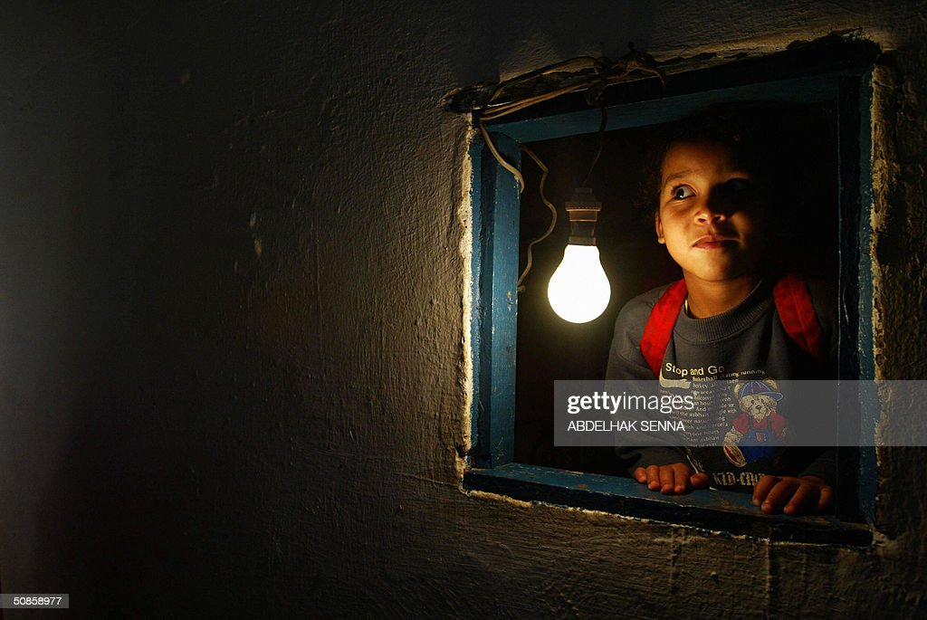 A Moroccan girl looks out the window of her makeshift home late 18 May 2004 in a shantytown of Casablanca. The shack is lit with electricity provided in test areas by the utility LYDEC (Lyonnaise des Eaux de Casablanca). No electrical service is provided in shantytowns, and residents rely on communal street lighting, which they divert illegally to light their homes. In Casablanca alone, 400,000 people live in shantytowns.