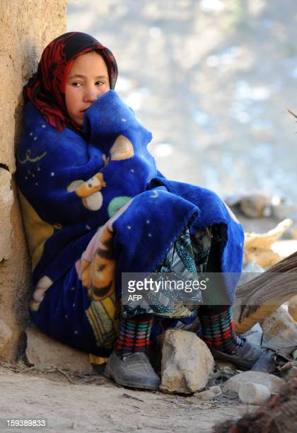 A Moroccan girl sits outside her house in Anfgou in the High Atlas mountains on January 12 2013 More than 20 tons of food and hundreds of duvets and...