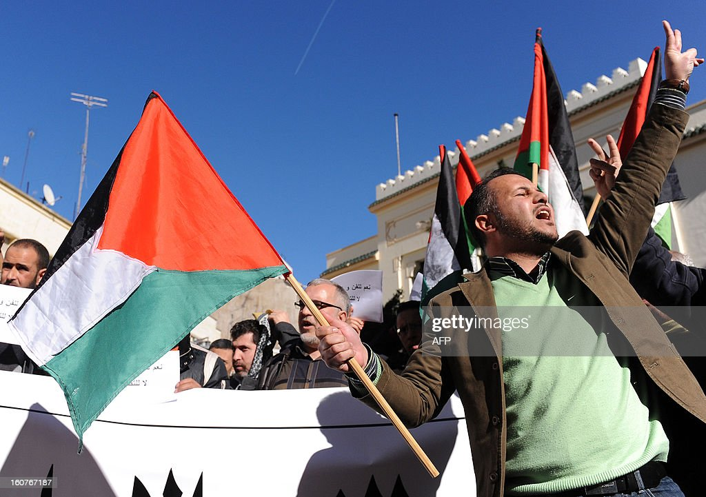 Moroccan Islamist protestors hold the Palestinian flag during a demonstration against a documentary movie about the Jews of Morocco by French-Moroccan director Kamal Hachkar on February 5, 2013 outside the cinema Roxy during the Morocco Cinema Festival in Tangiers. There were some 250 thousand Jews in the North African country in the first half of the 20th century. Today the community is big of about 3,000 people.