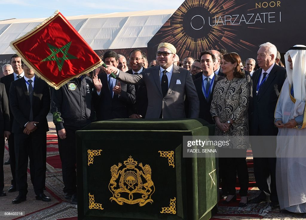 Moroccan King Mohammed VI (C) waves the Moroccan flag as he inaugurates the Noor 1 Concentrated Solar Power (CSP) plant, some 20 kilometres (12.5 miles) outside the central Moroccan town of Ouarzazate as French minister for Ecology, Sustainable Development and Energy Segolene Royal (3R) watches on, on February 4, 2016. Noor 1 is one of the largest solar plants in the world, which is the first stage of a larger project designed to boost renewable energy production in Morocco. / AFP / FADEL