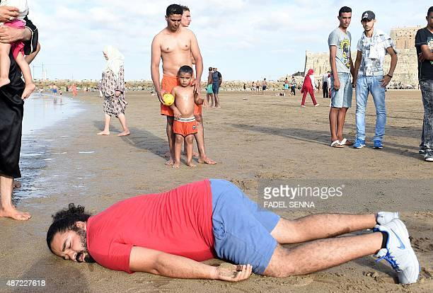 A Moroccan man adopts the position of the lifeless body of Syrian threeyearold Aylan Kurdi who drowned while fleeing the Syrian war during a rally to...