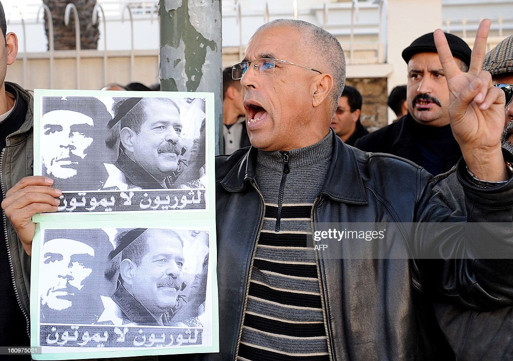 A Moroccan man flashes the sign for victory as he shouts slogans during a demonstration against the murder of Tunisian opposition leader Chokri Belaid (portrait-R) in front of the Tunisian embassy in Rabat, on February 8, 2013. The opposition has accused Ennahda, the Islamist party that dominates the ruling coalition, of eliminating the outspoken government critic after months of simmering tensions between liberals and Islamists over the future direction of the once proudly secular Muslim nation.