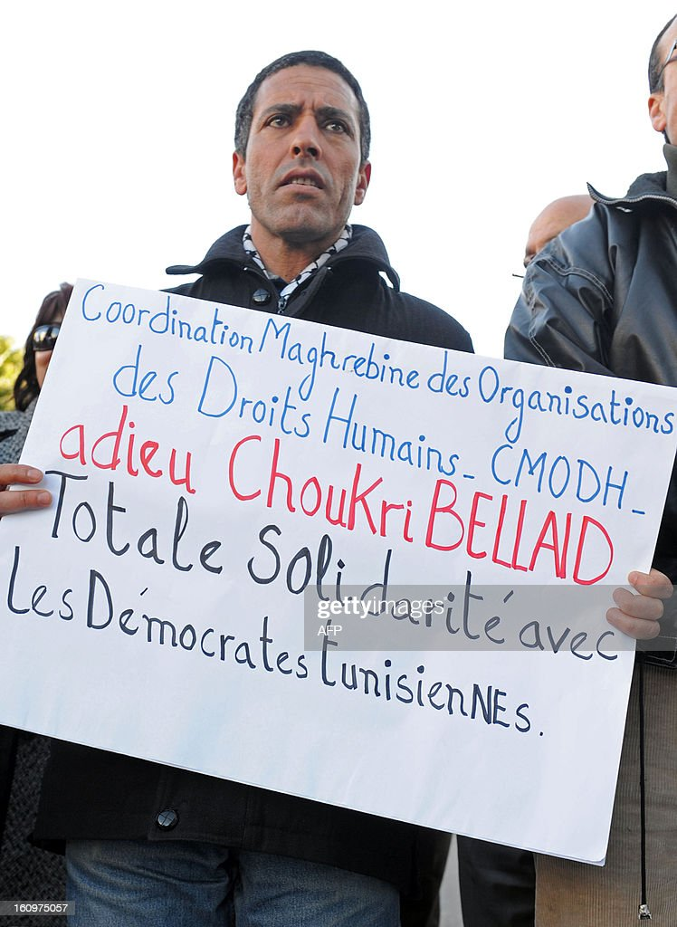 A Moroccan man holds a banner during a demonstration against the murder of Tunisian opposition leader Chokri Belaid in front of the Tunisian embassy in Rabat, on February 8, 2013. The opposition has accused Ennahda, the Islamist party that dominates the ruling coalition, of eliminating the outspoken government critic after months of simmering tensions between liberals and Islamists over the future direction of the once proudly secular Muslim nation. AFP PHOTO/FADEL SENNA