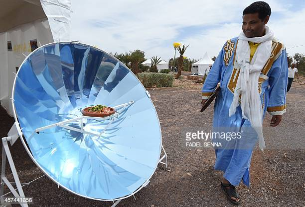 A Moroccan man looks at a solar oven cooking a tajine in a traditional pot during the first edition of the 'Morocco Solar Festival' in Ouarzazate on...