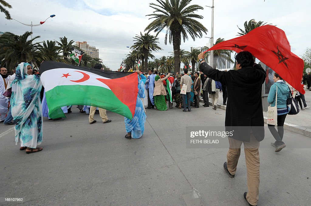 A Moroccan man waves his national flags near supporters of the Polisario Front separatist movement holding the flag of their party during a demonstration at the closing of the World Social Forum (WSF) on March 30, 2013 in Tunis. AFP PHOTO / FETHI BELAID