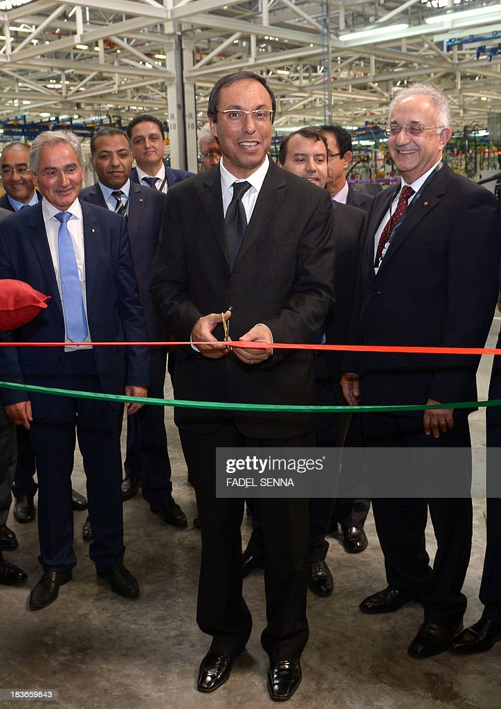 Moroccan Minister of Industry Abdelkader Amara (C), cuts a ribbon during the opening ceremony of the inauguration of the second phase of the Renault factory in Tangier on October 8, 2013. This second unit, which will oversee the production of the Dacio Sandero car, will allow the French manufacturer to double its production, to reach 340,000 vehicles per year in 2014, which will make Renault Tangier 'the biggest factory' of its type in Africa, according to its managers. AFP PHOTO /FADEL SENNA