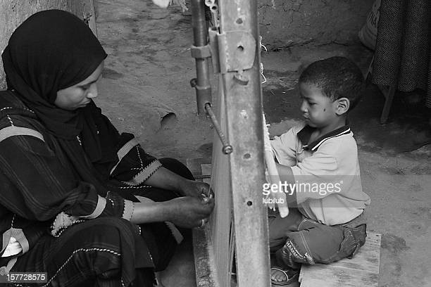 Moroccan mère et son tressage sur les côtés de Métier à tisser