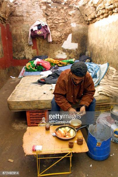 A Moroccan prepares a meal in his shack 23 January 2001 in the shanty town of La loma de la Mezquita near El Ejido where a group of Moroccans mainly...