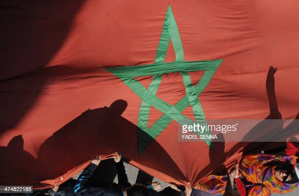 Moroccan protesters hold a giant national flag during a demonstration outside the French embassy in Rabat on February 25 following diplomatic...
