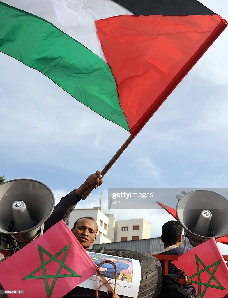 A Moroccan protestor waves a Palestinian flag next to loudspeakers bearing Moroccan flags during a demonstration in Casablanca on November 25, 2012, in support of the Palestinians after Israel's devastating eight-day bombardment of the Gaza Strip. A parallel demonstration took place in the city of Rabat where over 45,000 protestors condemned Israel for 'crimes against humanity' during the assault that killed more than 160 Gazans, and criticised Washington for supporting the Jewish state.