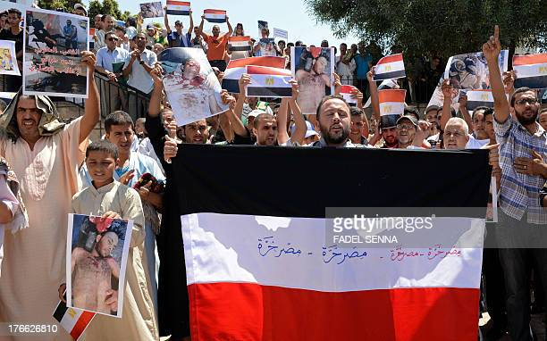 Moroccan protestors hold pictures of dead Egyptian demonstrators and Egyptian flags as they chant slogans during a rally in Rabat against the...