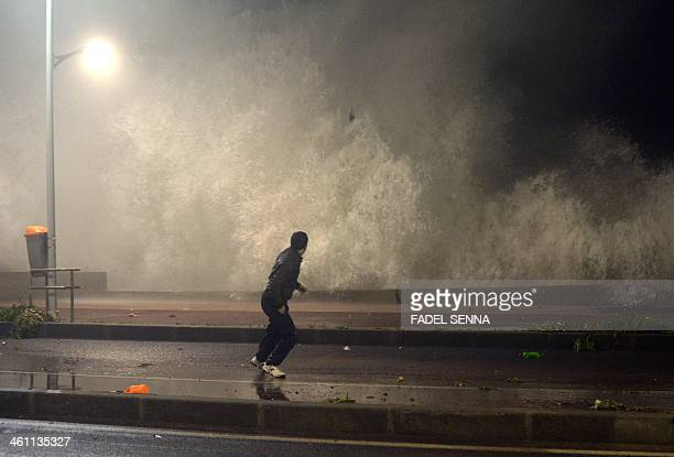 A Moroccan resident runs as a huge wave crashes along the Atlantic costal road in Rabat during high tide on January 7 2014 The wave was some 8 meters...