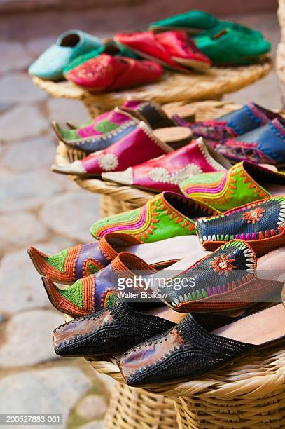 Moroccan slippers for sale displayed on woven stools