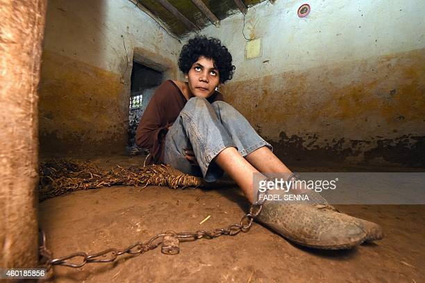 Moroccan Soukaina B a 21yearold woman suffering from a mental disorder sits chained to a post on the ground of her family's horse stable in a village...
