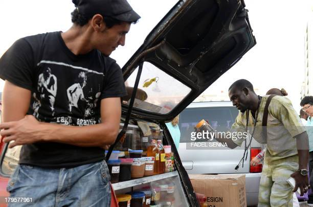 Moroccan street vendor watches a Senegalese immigrant as he checks one of his products in Rabat on August 23 2013 Following the death of a Senegalese...