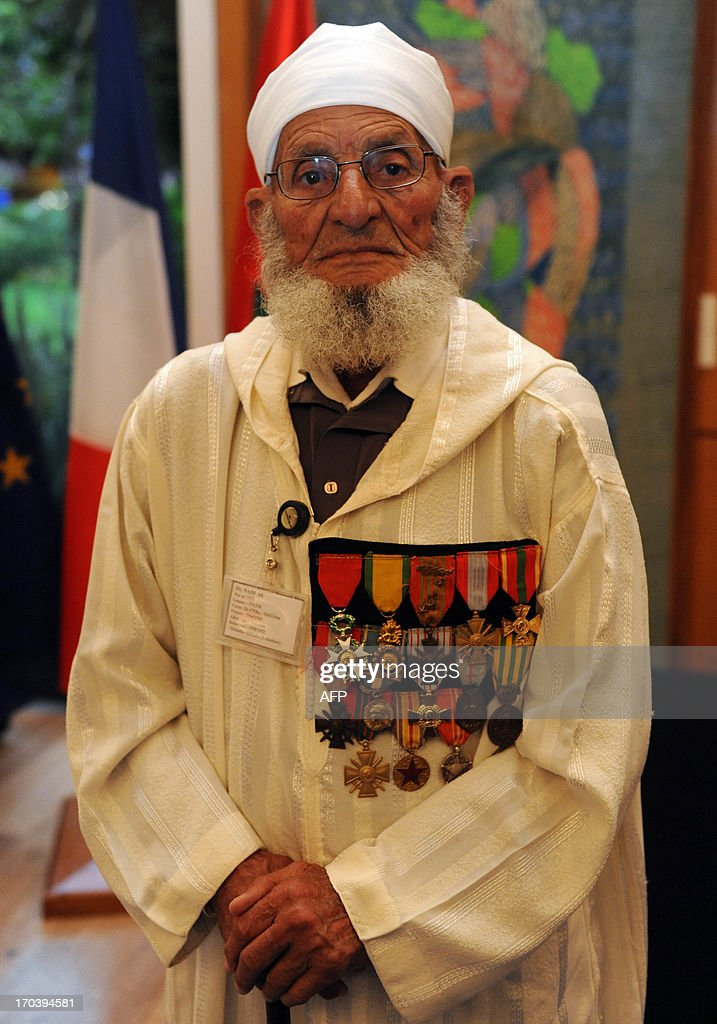 Moroccan veterans who fought for France during World War II and Indochina war listen during a ceremony presided by French Minister in charge of Veteran Affairs Kader Arif at the residence of the French embassy where Moroccan veterans who served in the French army are being decorated for their bravery on June 12, 2013 in Rabat.