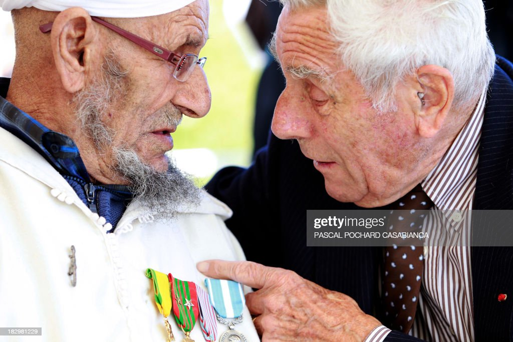 A Moroccan war veteran, who served as 'Moroccan Goumiers' in the French Army of Africa during WWII, speaks with a French war veteran on October 3, 2013 in Bastia during an award ceremony marking the 70th anniversary of the liberation of the French island of Corsica in the Mediterranean Sea.