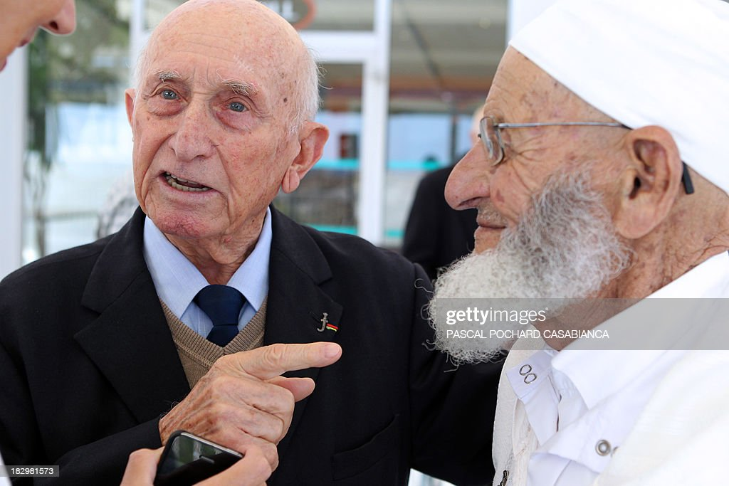A Moroccan war veteran (R), who served as 'Moroccan Goumiers' in the French Army of Africa during WWII, speaks with a French war veteran on October 3, 2013 in Bastia during an award ceremony marking the 70th anniversary of the liberation of the French island of Corsica in the Mediterranean Sea.
