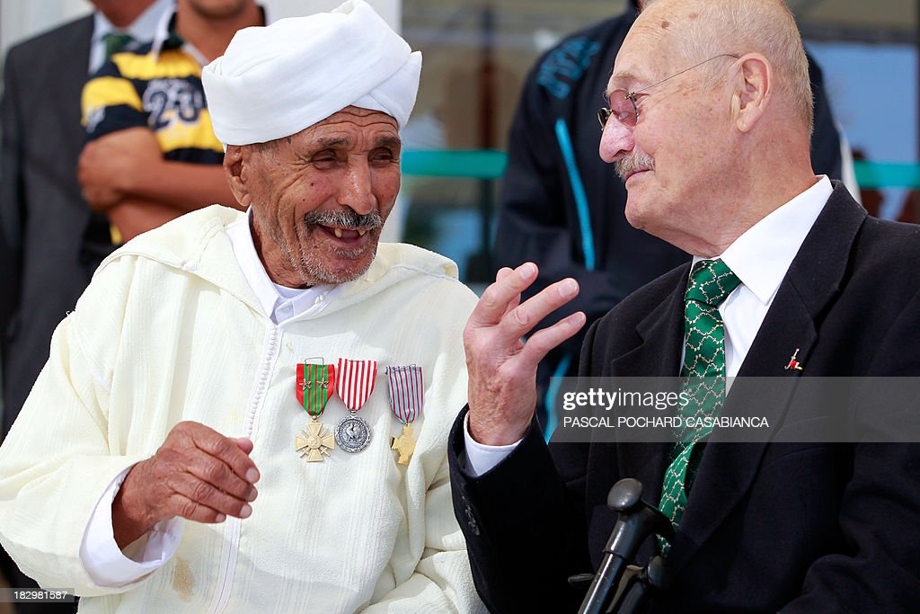 A Moroccan war veteran, who served as 'Moroccan Goumiers' in the French Army of Africa during WWII, speaks with a French war veteran on October 3, 2013 in Bastia during an award ceremony marking the 70th anniversary of the liberation of the French island of Corsica in the Mediterranean Sea. AFP PHOTO / PASCAL POCHARD-CASABIANCA
