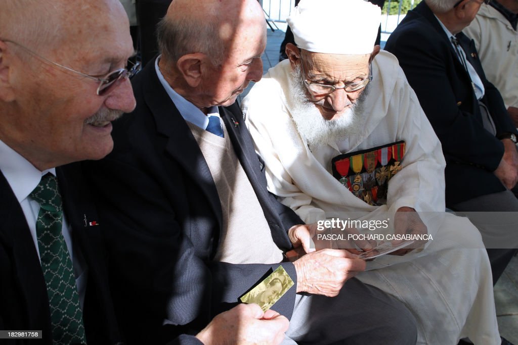 Moroccan war veterans, who served as 'Moroccan Goumiers' in the French Army of Africa during WWII, look at photographs with French war veterans on October 3, 2013 in Bastia during an award ceremony marking the 70th anniversary of the liberation of the French island of Corsica in the Mediterranean Sea. AFP PHOTO / PASCAL POCHARD-CASABIANCA