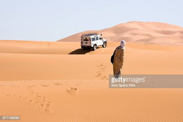 A Moroccan watches runners approaching the finish line from erg Chebbi dunes during the sixth and final stage of the 22nd Marathon des Sables between...